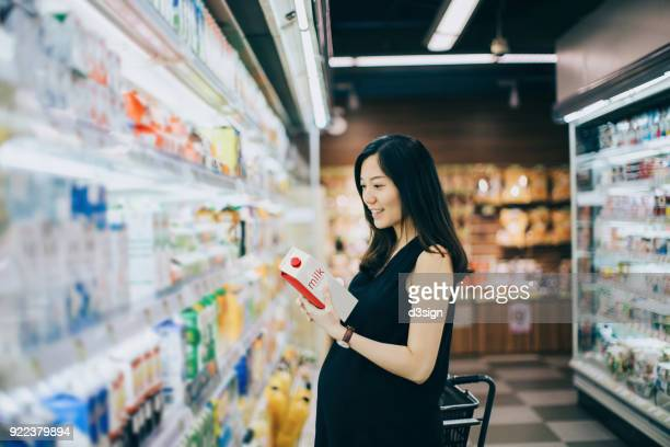 Asian pregnant woman grocery shopping in supermarket and holding a bottle of fresh milk