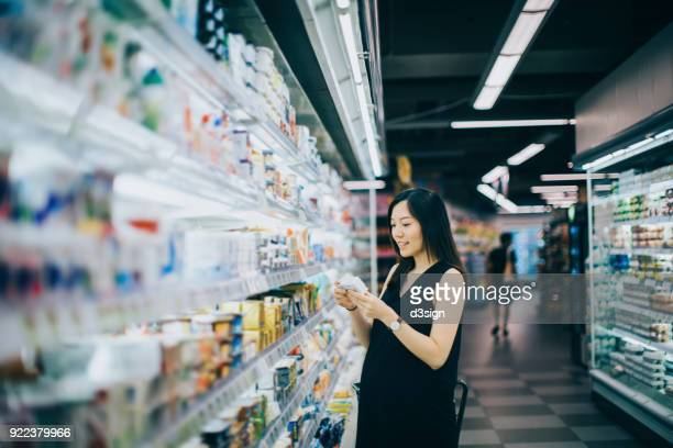 asian pregnant woman grocery shopping in supermarket and reading nutrition label on a packet of cheese - convenience store stock photos and pictures