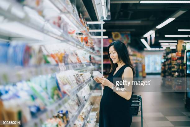 Asian pregnant woman grocery shopping in supermarket and reading the nutrient label on the packet of dairy product