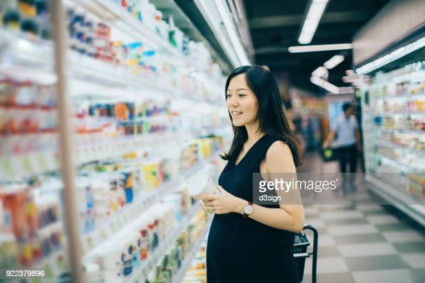 Asian pregnant woman shops in dairy section in supermarket and holding a bottle of yoghurt