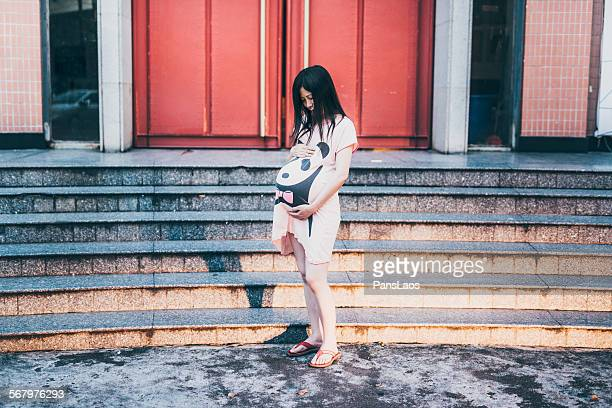 Asian pregnant woman standing in city