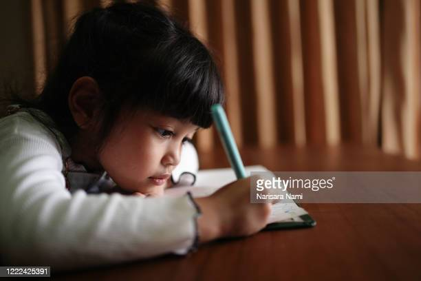 asian preschool child girl  doing a homework seriously at night. education and intelligence concept. - homeschool stock pictures, royalty-free photos & images