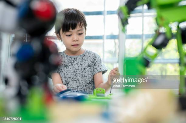 asian preschool girls wearing hearing aids while learning on a robot assembly in classroom. improve kids learning skill and motivative concetps. - stem stock pictures, royalty-free photos & images