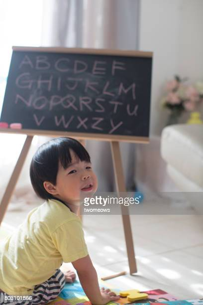 Asian preschool student learning alphabets.