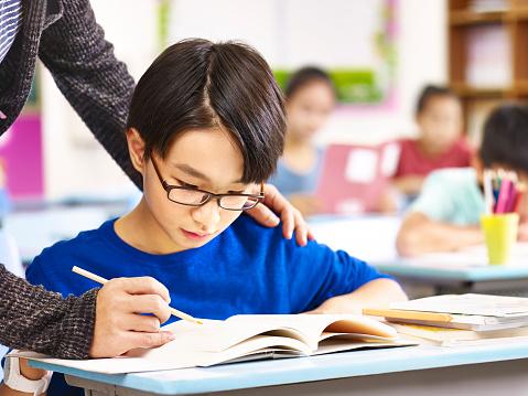 asian pupil getting help from teacher in class 859280934