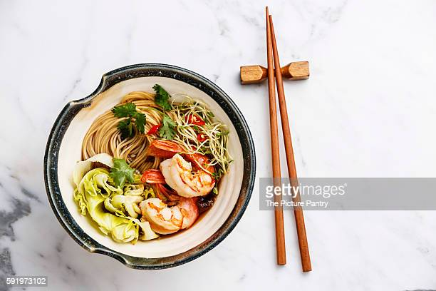 Asian Ramen noodles with Prawns and greens on white marble background