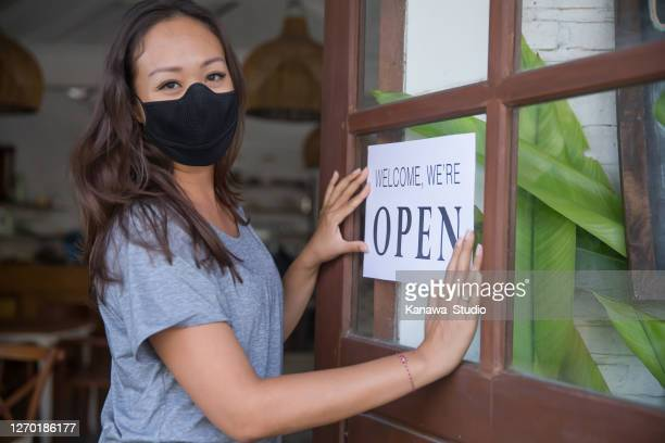 asian restaurant manager holding an open poster sign at the entrance door - opening event stock pictures, royalty-free photos & images