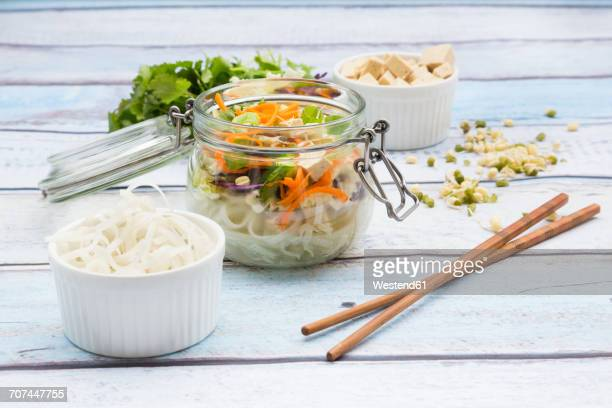 Asian rice noodle soup with vegetables and tofu in jar