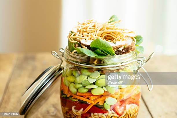 asian salad in a jar with ramen noodles, red pepper, snow pea pods, carrots, edamame, shiitake mushrooms, salad greens, fried chow mien noodles and dressing - soy sauce stock photos and pictures