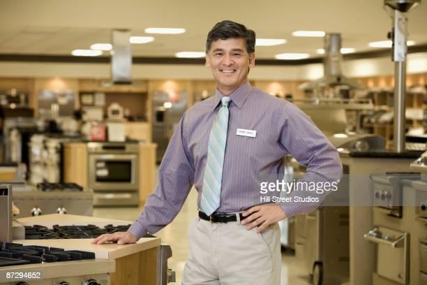 Asian salesman in appliance showroom