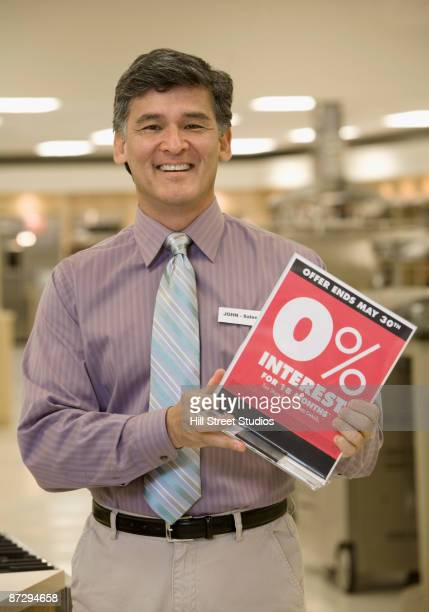 Asian salesman with promotional sign in showroom
