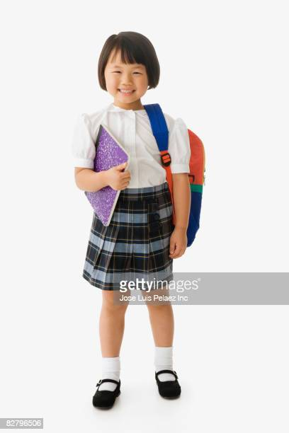 Asian school girl in uniform holding backpack and notebook