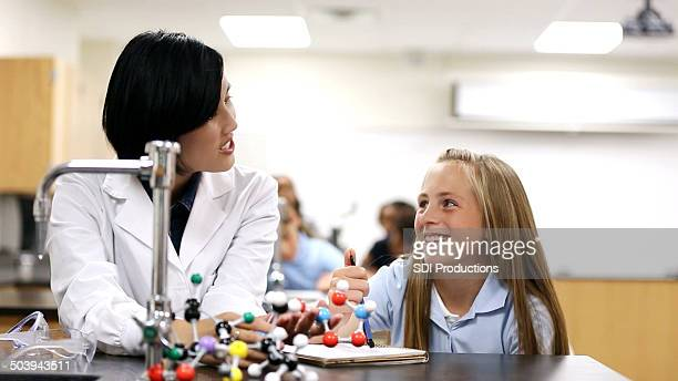 Asian science teacher using atom model to help student