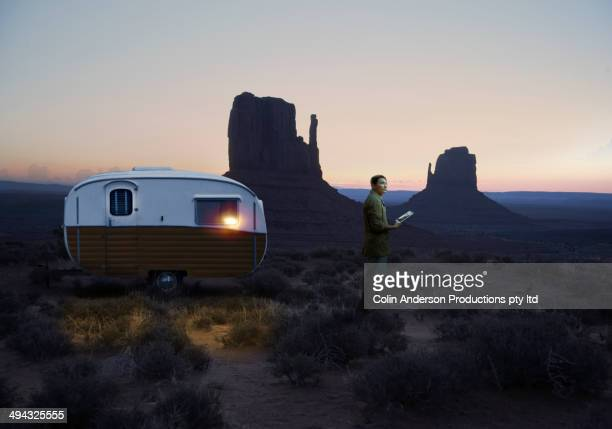 Asian scientist parking trailer in desert landscape