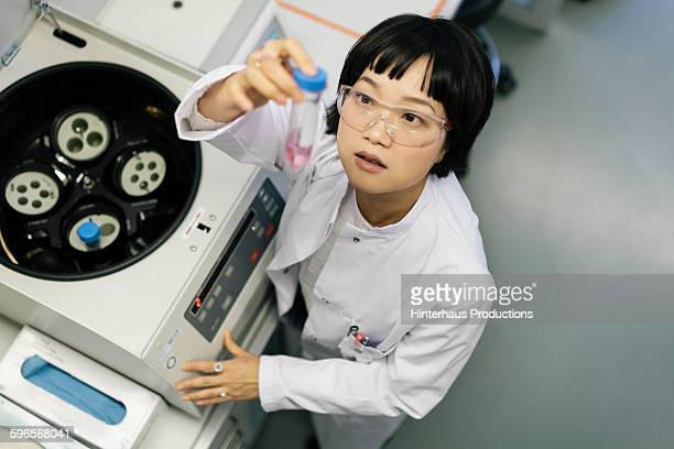 Asian scientist taking a look at a flask
