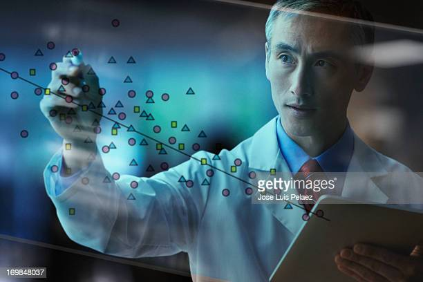 Asian scientist writing on glass board