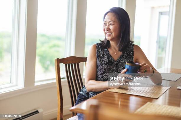 Asian senior adult woman sitting at dining table smiling while looking out window with hot drink in hand