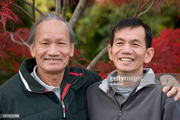 asian senior and adult male relatives embracing for portrait outdoors - vietnamese ethnicity stock pictures, royalty-free photos & images