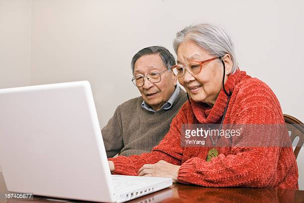 Asian Senior Chinese Couple Using Laptop Computer for Family Communication