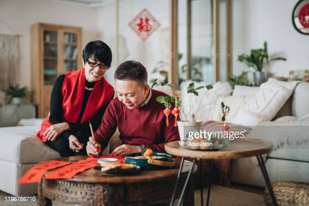 asian senior couple practising chinese calligraphy for chinese new year fai chun (auspicious messages) by writing it on a piece of red paper - chinese language stock pictures, royalty-free photos & images