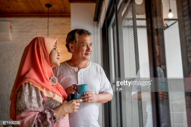 asian senior couple standing by the window in a living room - muslim couple stock pictures, royalty-free photos & images