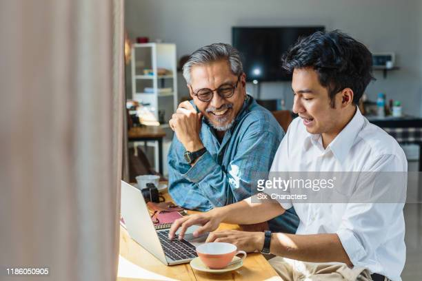 asian senior father and his adult son using laptop computer while sitting at home - son stock pictures, royalty-free photos & images