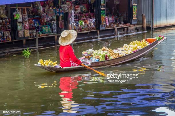 asian senior female selling many thai fruit at damnoen saduak floating market in ratchaburi near bangkok - asiatisches langboot stock-fotos und bilder
