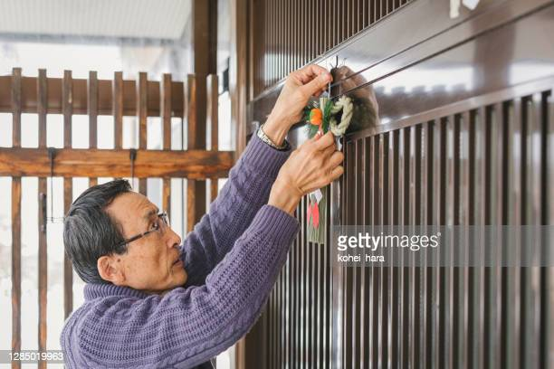 asian senior man decorating shrines and gates with shimenawa ropes for the new year at the entrance - 70 year old man stock pictures, royalty-free photos & images