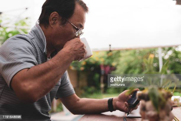 asian senior man enjoying videos on smartphone - adult videos japan stock pictures, royalty-free photos & images