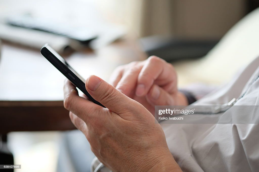 Asian senior man is typing text on smart phone. : ストックフォト