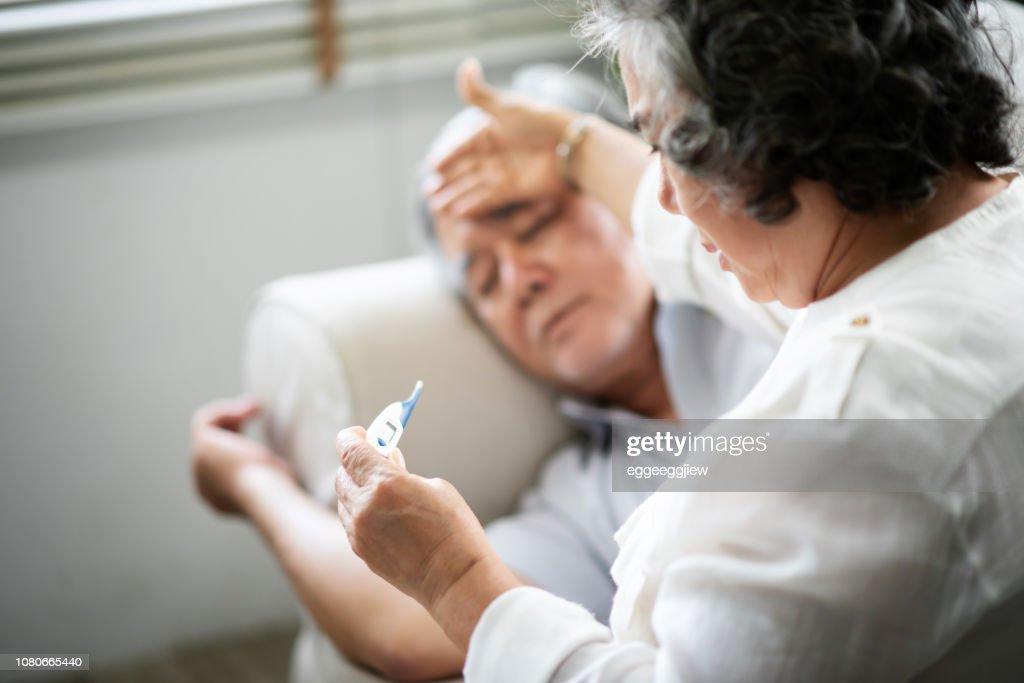 Asiatische Senior Mann auf Sofa, während seine Frau halten und auf der Suche nach Thermometer liegen. : Stock-Foto