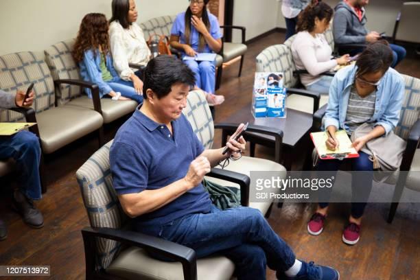 un anciano asiático espera una cita con el médico - atestado fotografías e imágenes de stock