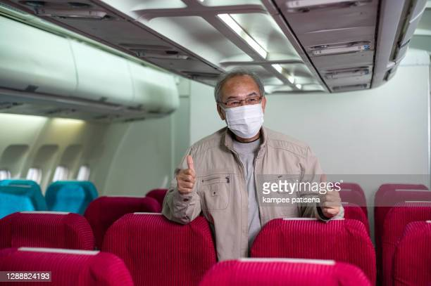 asian senior man wearing a face mask protect covid-19 on an airplane - chairperson stock pictures, royalty-free photos & images