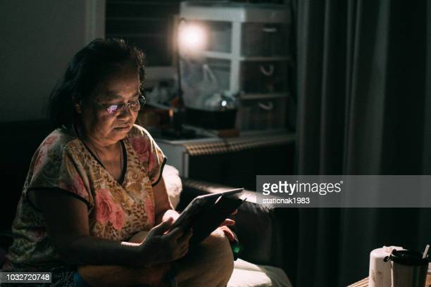 Asian senior woman sitting on the sofa and looking at photo.