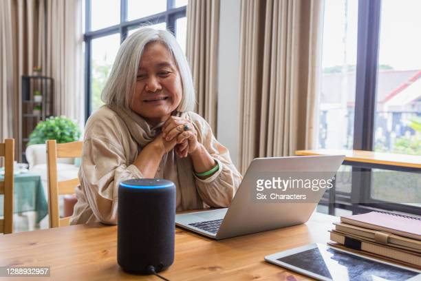 asian senior women working with laptop computer and using smart speakers while setting in living room at home - 60 64 years stock pictures, royalty-free photos & images