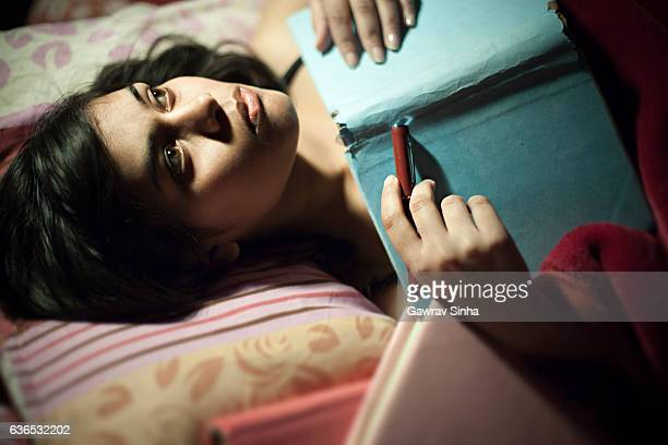 Asian serene girl thinking and lying on bed with book.