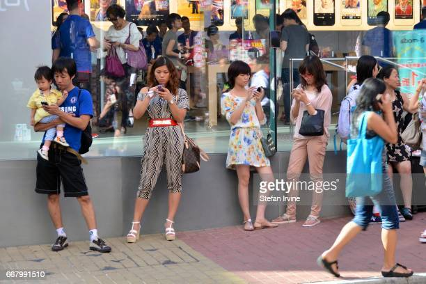 Asian shoppers using iPhone smartphones outside the Apple Store in Hong Kong