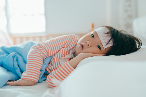 Asian sick little girl lying in bed with a high fever - gettyimageskorea