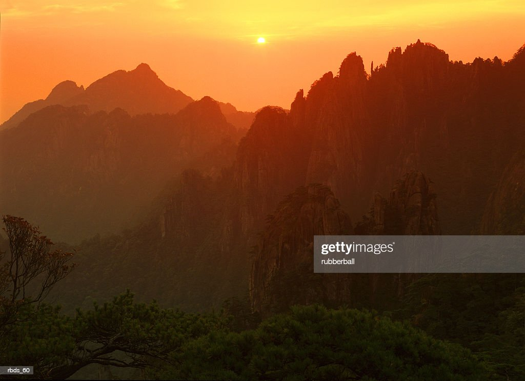 asian silhouetted mountains against a yellow and orange sunset : Stockfoto