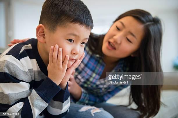 asian sister comforting sad brother on sofa - 姉妹 ストックフォトと画像
