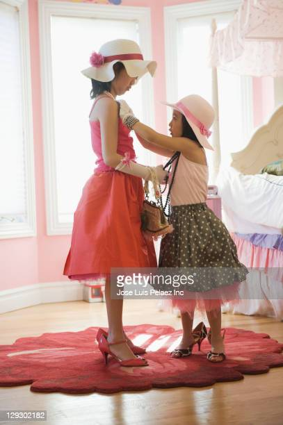 Asian sisters playing dress up