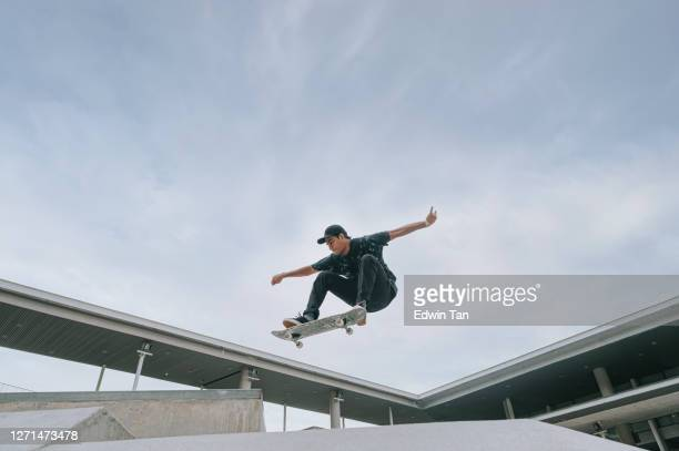 asian skateboarder in action mid air - skating stock pictures, royalty-free photos & images