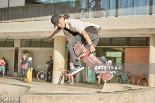 asian skateboarder in action - ollie pictures stock pictures, royalty-free photos & images