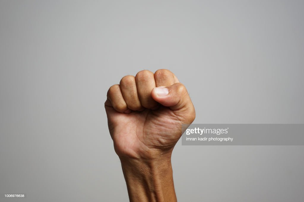 Asian skin showing fists in right hand with grey background : Stock Photo