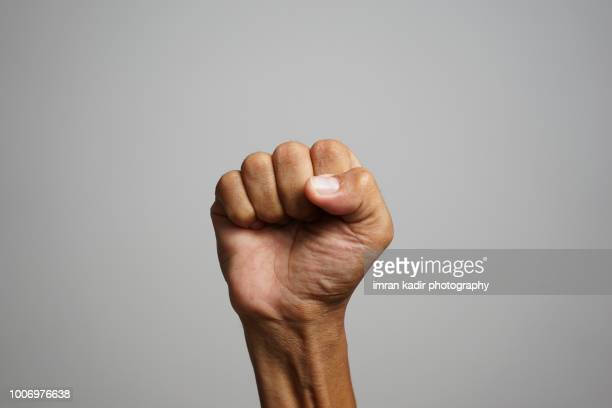 asian skin showing fists in right hand with grey background - march stock-fotos und bilder