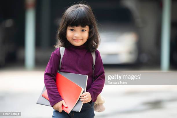 asian smile cute child girl with book is ready for going to kindergarten school for the first time. - first occurrence stock pictures, royalty-free photos & images