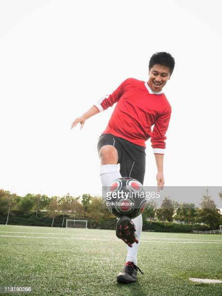 Asian soccer player practicing with ball on soccer field