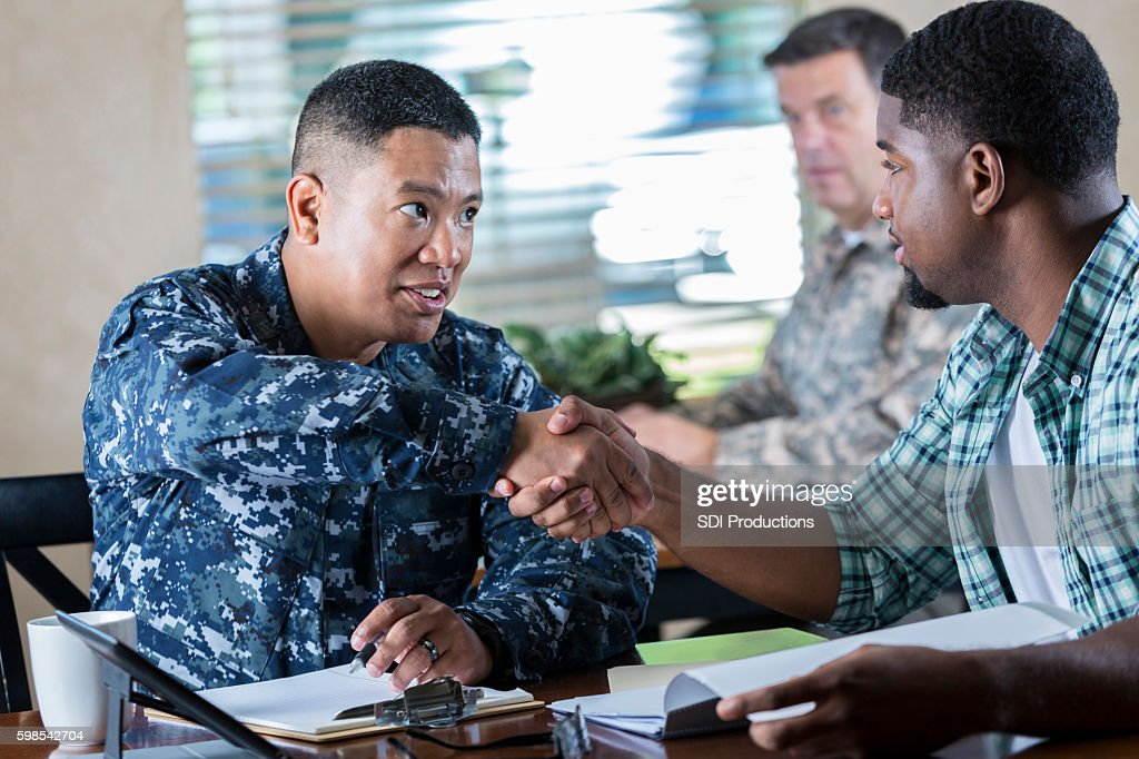 Asian soldier meeting with young man at military recruitment event : Stock Photo