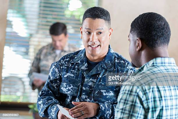 Asian soldier recruiting young man in military office