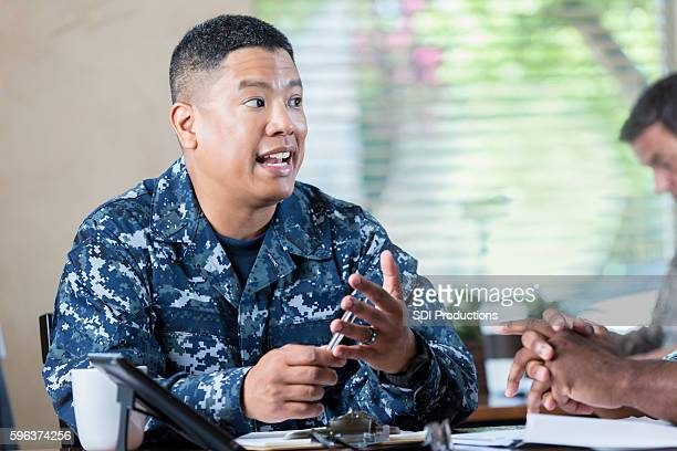 asian soldier talking to  man during military recruitment event - american influenced stock photos and pictures